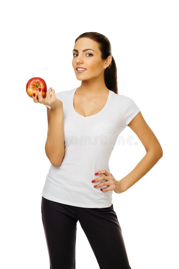 Schöne junge glückliche brunette Frau im weißen T-Shirt hält Apfel Stände, die das Lächeln auf dem weißen Hintergrund lokalisiert lizenzfreie stockbilder