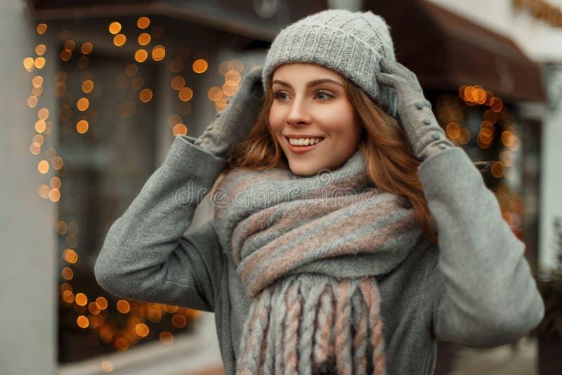 Schöne junge glückliche Frau, die in einem grauen Mantel lächelt lizenzfreie stockfotos