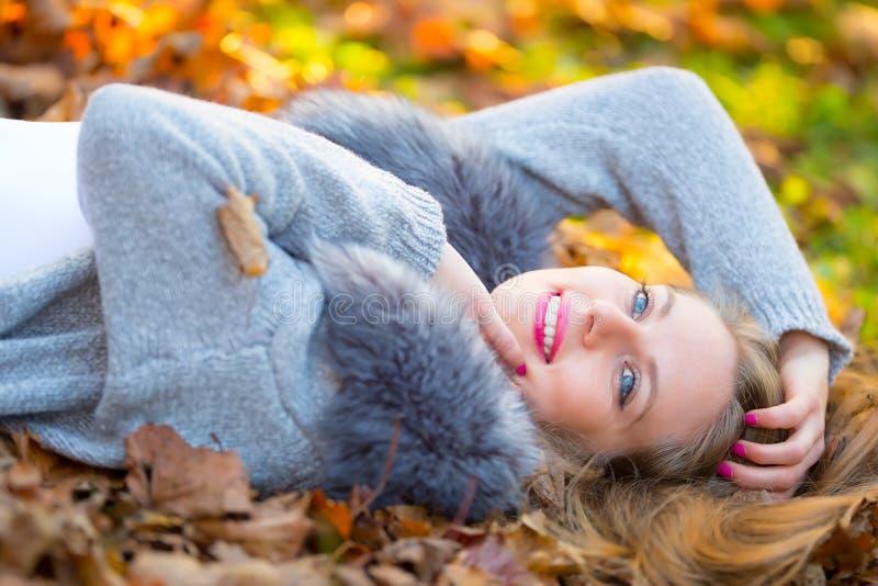 Schöne junge glückliche Frau, die im Herbstpark liegt lizenzfreies stockbild