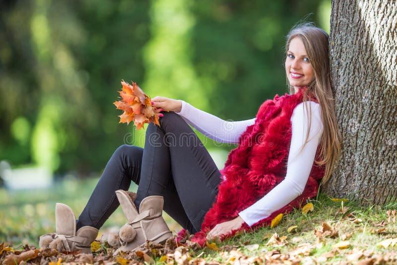 Schöne junge glückliche Frau, die im Herbstpark sitzt lizenzfreies stockbild