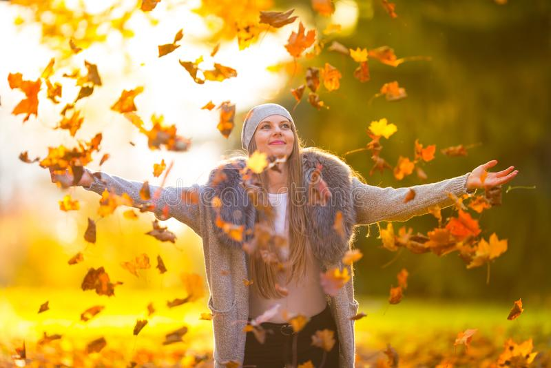 Schöne junge glückliche Frau, die mit Herbstlaub spielt stockbild