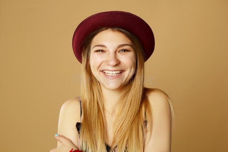 Schöne junge glückliche smileyfrau, die im Studio über Gelb aufwirft stockfoto