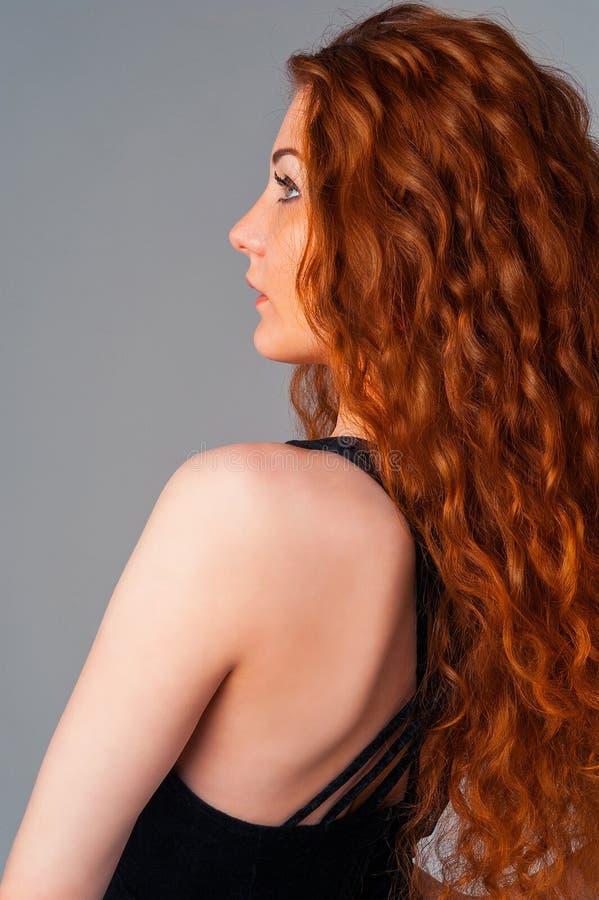 Schöne junge hübsche Frau mit dem perfekten langen roten Haarschauen stockfotos