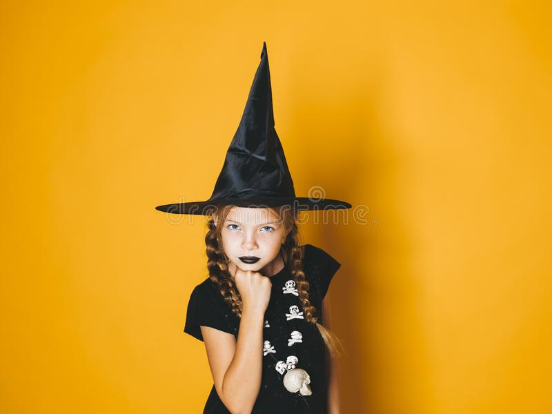 Schöne junge Halloween-Hexe auf orange Hintergrund mit schwarzem Hut lizenzfreie stockbilder