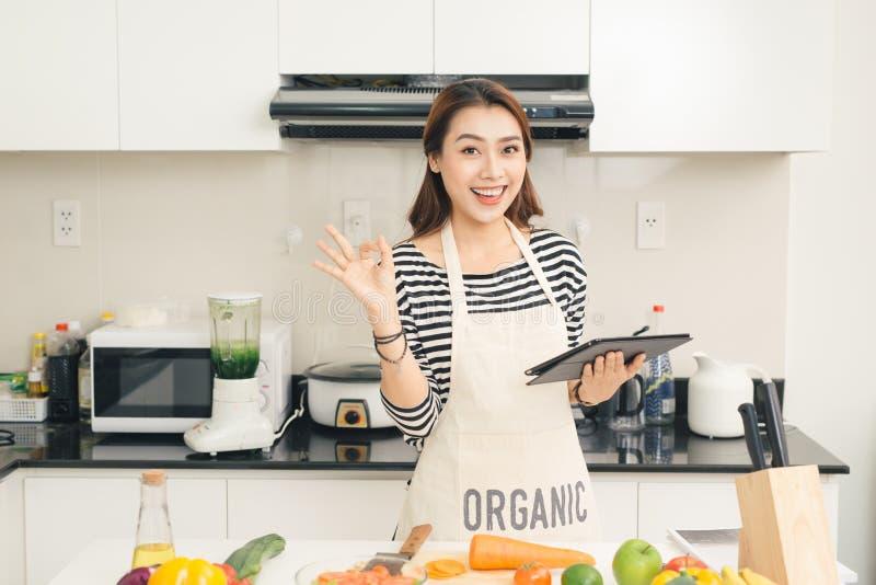 Schöne junge Hausfraufrau mit Tablet-Computer herein kochend lizenzfreie stockfotos