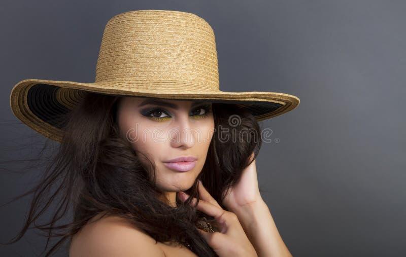 Schöne junge hispanische Frauen-tragender Strohhut lizenzfreie stockfotografie