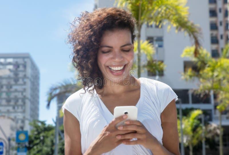 Schöne junge hispanische Frauenmitteilung telefonisch stockbilder