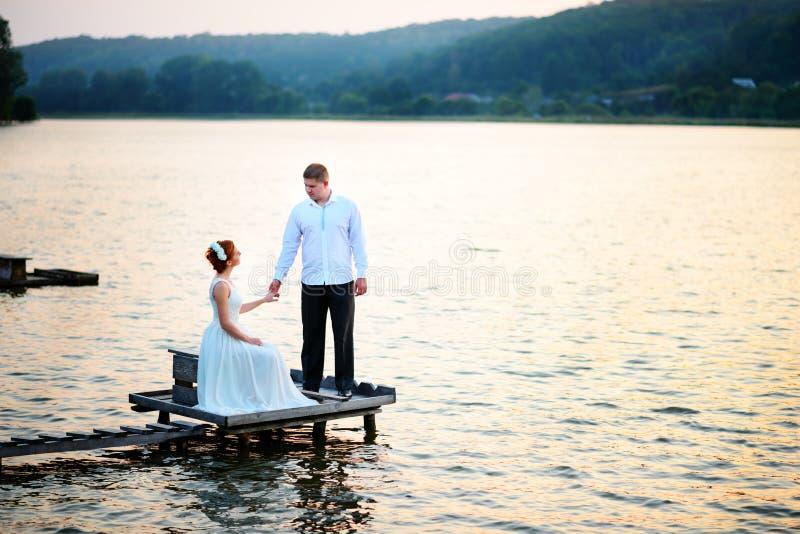 Schöne junge Hochzeitspaare, -braut und -bräutigam, die auf See b aufwirft stockbilder