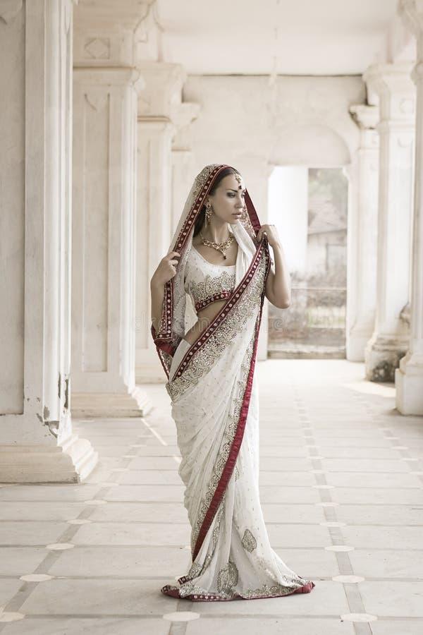 Schöne junge indische Frau in der traditionellen Kleidung mit Braut stockfotos