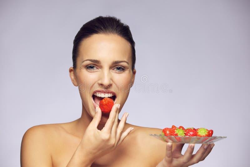 Schöne junge kaukasische Frau, die gesunde Früchte isst stockbild