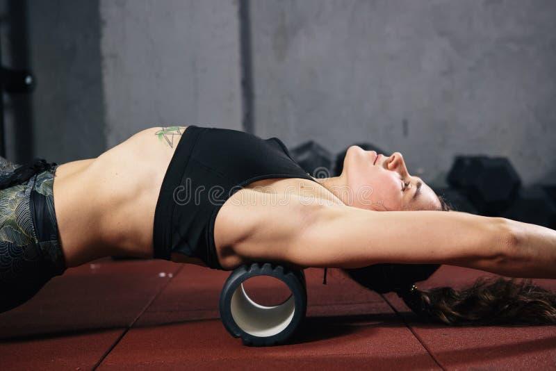 Schöne junge kaukasische Frauensportlerin benutzt einen Schaumrolle Massager für Entspannung und dehnt Muskeln und Rückenschmerze stockbild