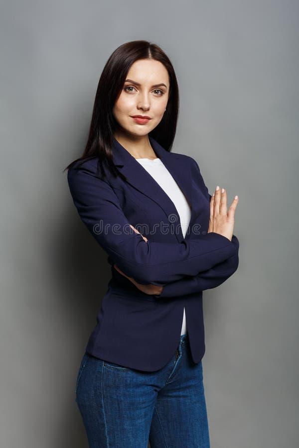 Schöne junge kaukasische Geschäftsfrauatelieraufnahme auf Graurückseite lizenzfreies stockfoto