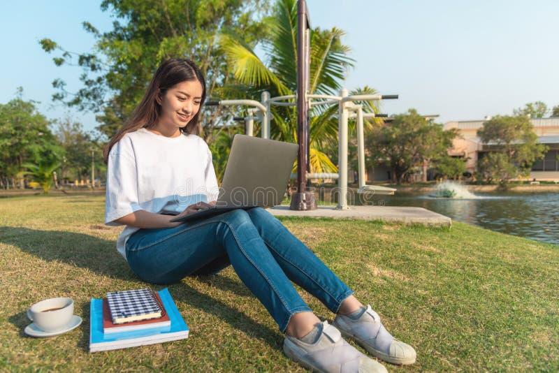 Schöne junge lächelnde Frau, die öffentlich Park der Tablette verwendet lizenzfreie stockfotografie
