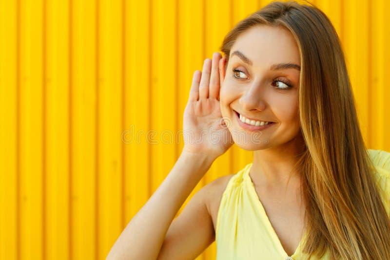 Schöne junge lächelnde Frau, die auf Geheimnis über gelbem Ba hört stockfotos