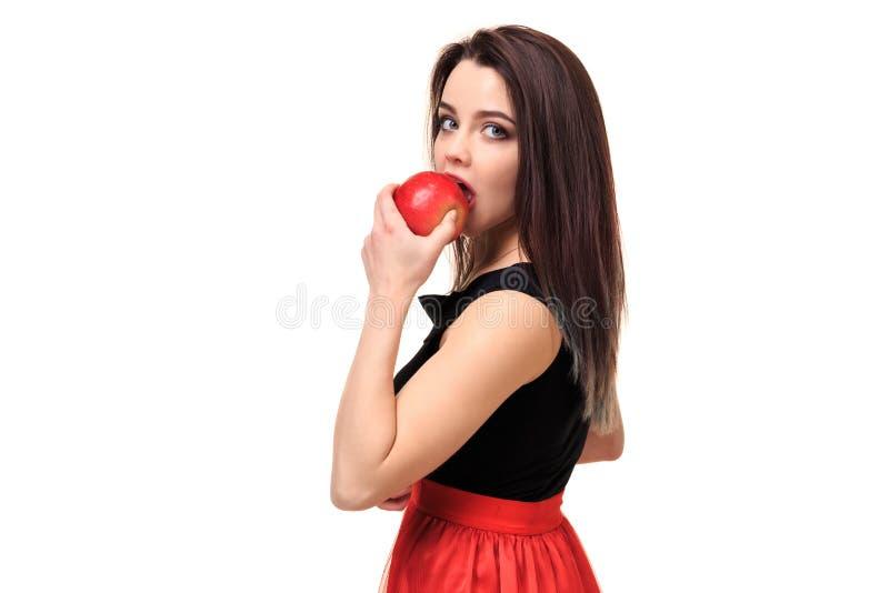 Schöne junge lächelnde Frau, die einen Apfel in ihren Händen auf einer weißen Hintergrundisolierung hält lizenzfreie stockfotos