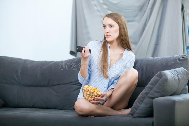 Schöne junge lächelnde Frau, die einen Film im Bett aufpasst und Popcorn isst stockbilder
