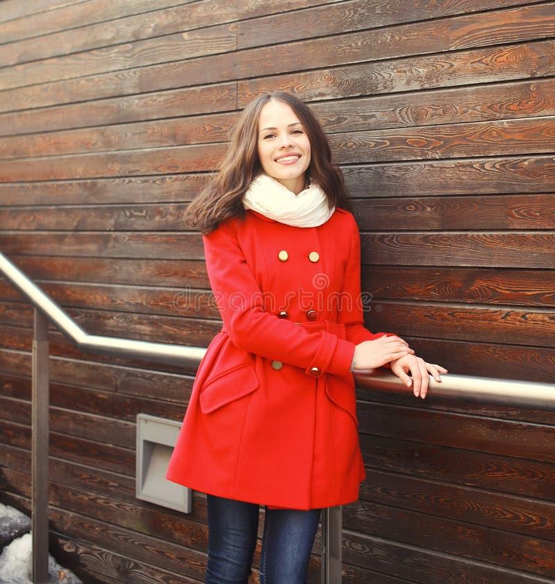 Schöne junge lächelnde Frau, die einen roten Mantel und einen Schal trägt stockfoto