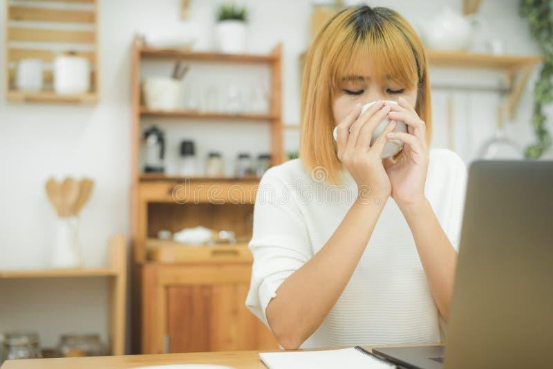 Schöne junge lächelnde Frau, die an Laptop beim Genießen arbeitet, den warmen Kaffee trinkend, der zu Hause in einem Wohnzimmer s stockbilder