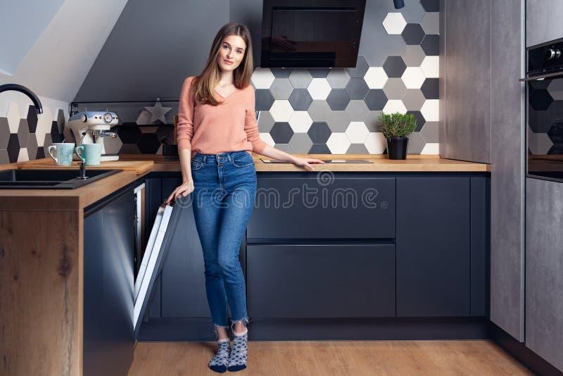 Schöne junge lächelnde Frau, die Teller in der Küche tut stockbilder