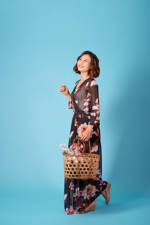 Schöne junge lächelnde Frau im Weinlesekleid, das einen Korb mit Blumen hält H?bsches junges M?dchen des Sommerportr?ts lizenzfreie stockbilder