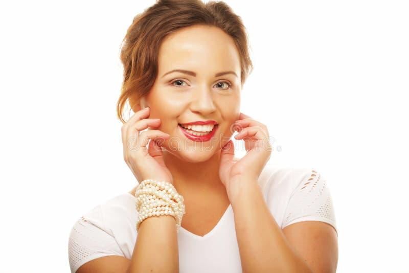 Schöne junge lächelnde Frau mit gesunder Haut und den roten Lippen über weißem Hintergrund stockbild
