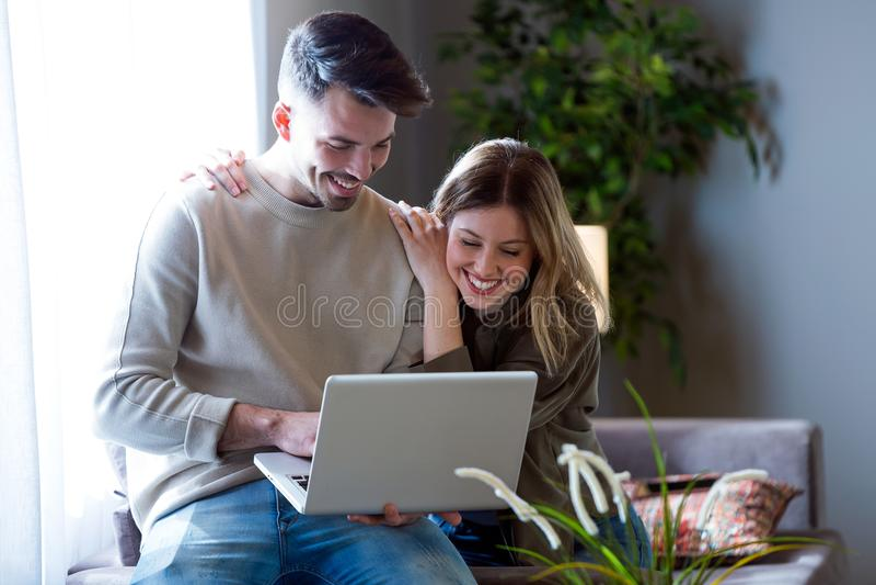Schöne junge lächelnde Paare unter Verwendung ihres Laptops zu Hause stockbilder