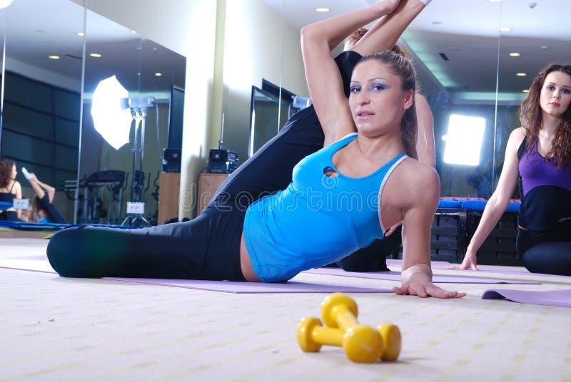 Schöne junge Mädchen, die in einer Gymnastik ausarbeiten lizenzfreie stockfotos
