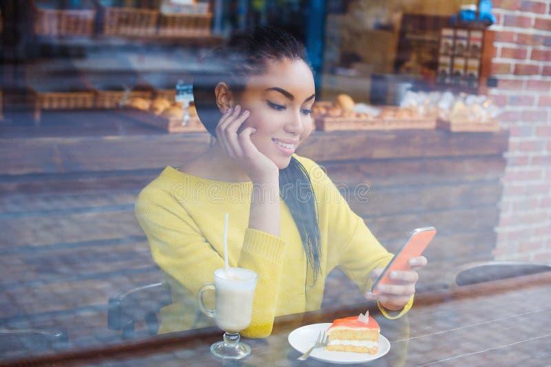 Schöne junge Mischrassefrau gesehen durch das Fenster der Bäckerei stockfotos