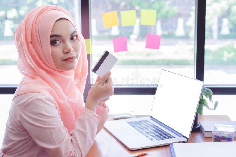 Schöne junge moslemische Frau, die eine Kreditkarte mit Laptopmodell im Büro zeigt stockfoto