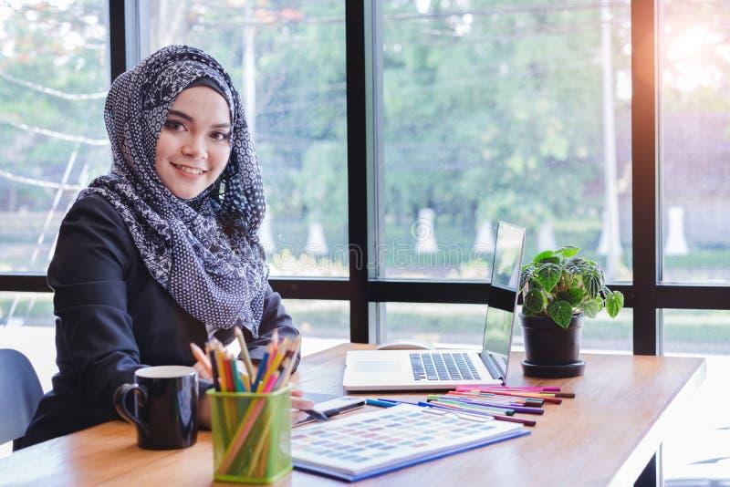 Schöne junge moslemische kreative Designerfrau, die Stifttabletten und -laptop verwendet lizenzfreie stockfotografie