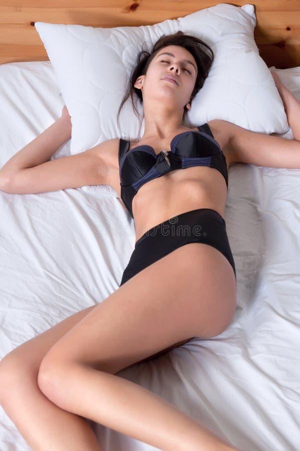 Schöne junge multi rassische Frau, die im Bett schläft stockbild