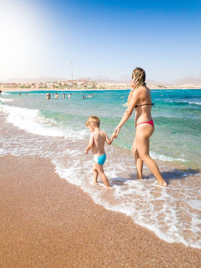 Schöne junge Mutter, die eigenhändig ihren kleinen Sohn hält und auf den sandigen Seestrand am hellen sonnigen Tag geht Kind lizenzfreies stockbild
