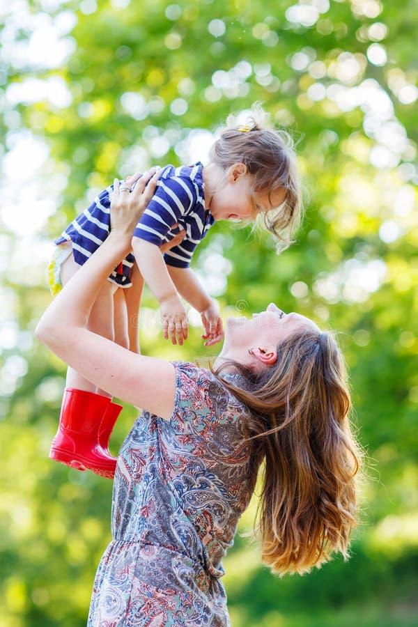 Schöne junge Mutter, die ihr glückliches Kleinkindmädchen in den Armen hält stockbilder