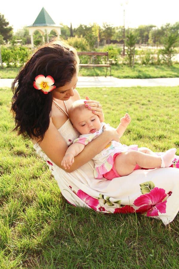 Schöne junge Mutter mit der entspannenden Tochter stockfoto