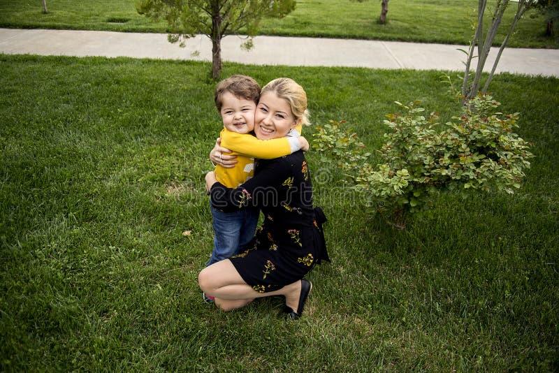 Schöne junge Mutter mit einem netten kleinen Sohn sie sind, das Umarmen glücklich und zeigen ihre reine Liebe lizenzfreie stockfotografie