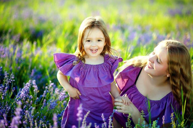 Schöne junge Mutter und ihre Tochter, die Spaß am Lavendelfeld hat Sohn gibt der Mama eine Blume stockbilder