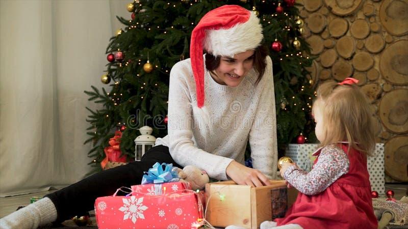Schöne, junge Mutter und Kind mit goldenen Spielwaren und Geschenken des Weihnachtsbaums Winterurlaube zu Hause feiernd lizenzfreie stockfotografie