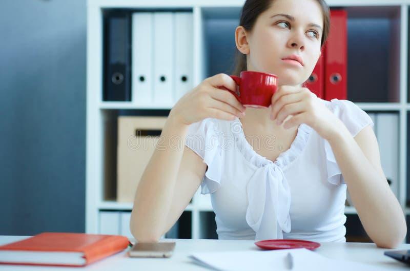 Schöne junge nachdenkliche Geschäftsfrau, die Tasse Kaffee hält lizenzfreie stockbilder