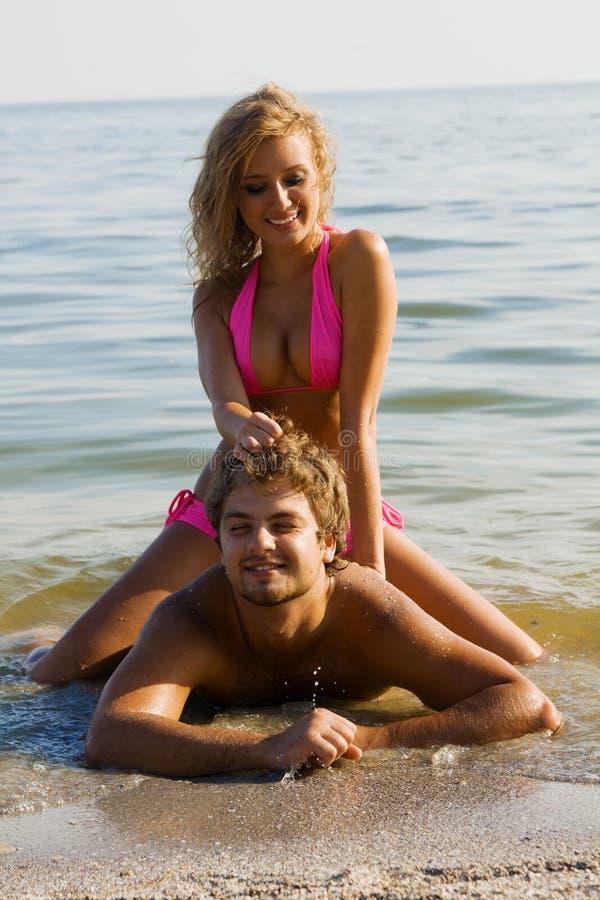 Schöne junge Paare auf der Küste stockbilder