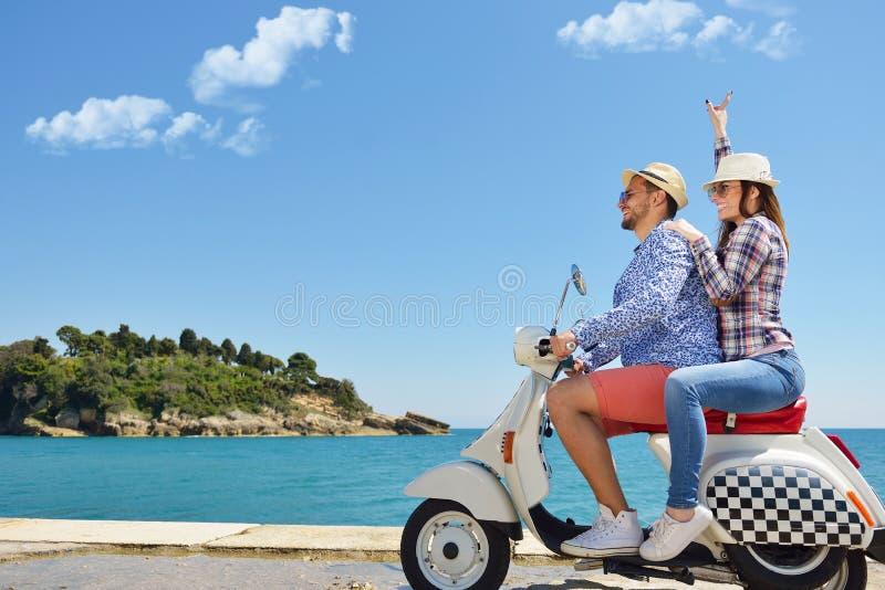 Schöne junge Paare in der Liebe, die Spaßreiten auf einem Roller in einer schönen Natur genießt und hat lizenzfreie stockfotografie