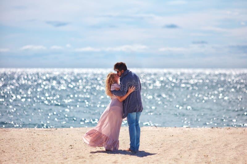 Schöne junge Paare, die auf sandigem Strand am Sommertag küssen lizenzfreies stockbild