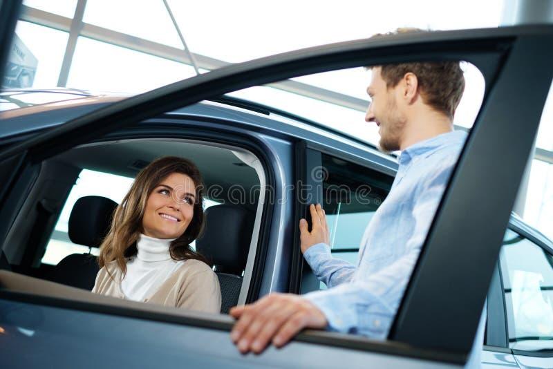 Schöne junge Paare, die einen Neuwagen dem Verkaufsstelleausstellungsraum betrachten stockbilder