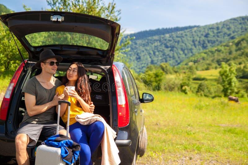 Schöne junge Paare, die im Stamm eines Autos und die schöne Landschaft bewundern auf dem Berg sitzen lizenzfreie stockfotos