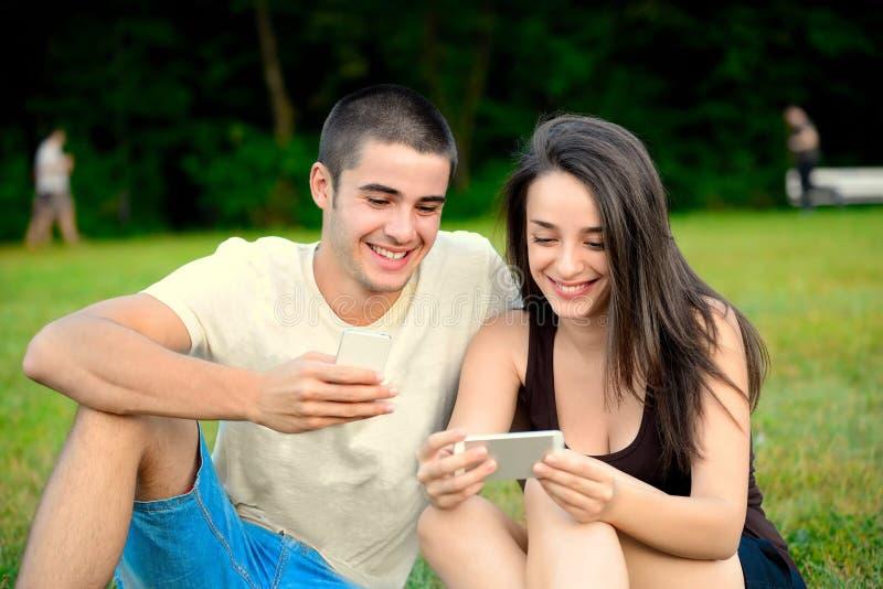 Schöne junge Paare, die intelligente Telefone und das Lachen grasen stockfotos