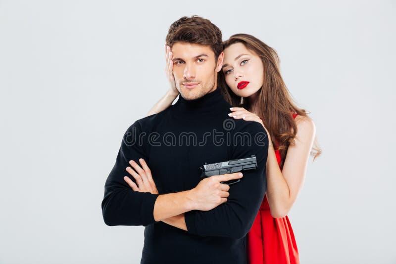 Schöne junge Paare, die mit Gewehr umarmen und aufwerfen stockfotos