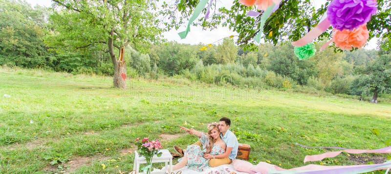 Schöne junge Paare, die Picknick in der Landschaft haben Glückliche Familie im Freien r stockfotografie