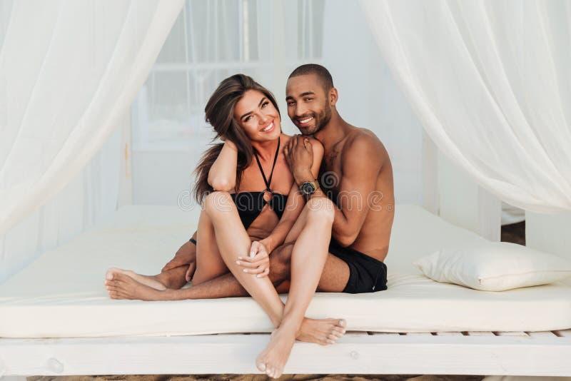 Schöne junge Paare, die zusammen auf weißem Bett sitzen lizenzfreie stockfotografie