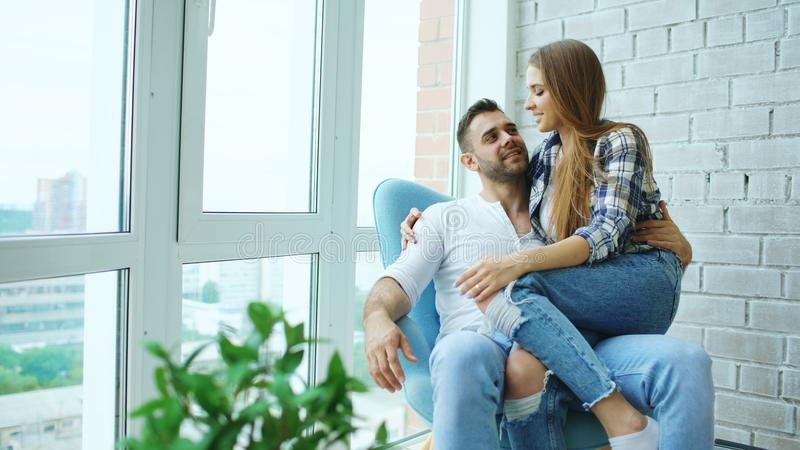 Schöne junge Paare entspannen sich das Sitzen auf Stuhl und das Genießen von Ansicht vom Balkon der neuen Dachbodenwohnung lizenzfreies stockfoto