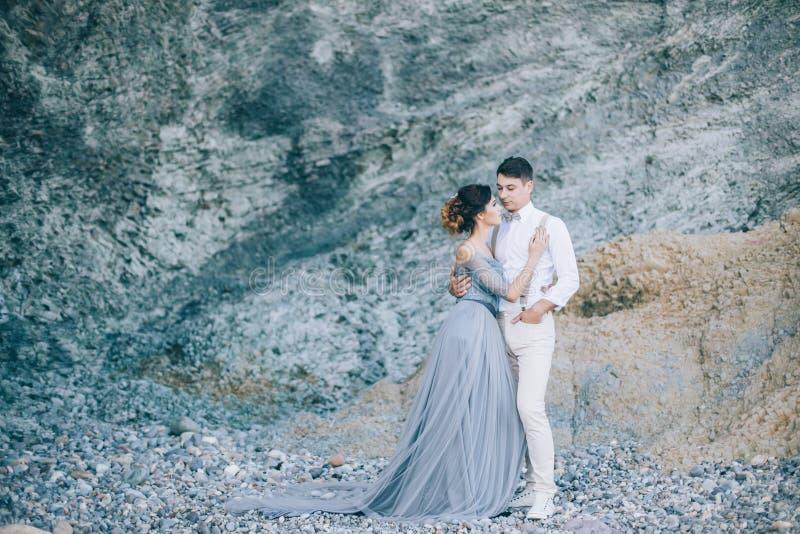 Schöne junge Paare an ihrem Hochzeitstag durch das Meer nahe dem Felsen Glück, Lebensstil, Familie lizenzfreies stockfoto