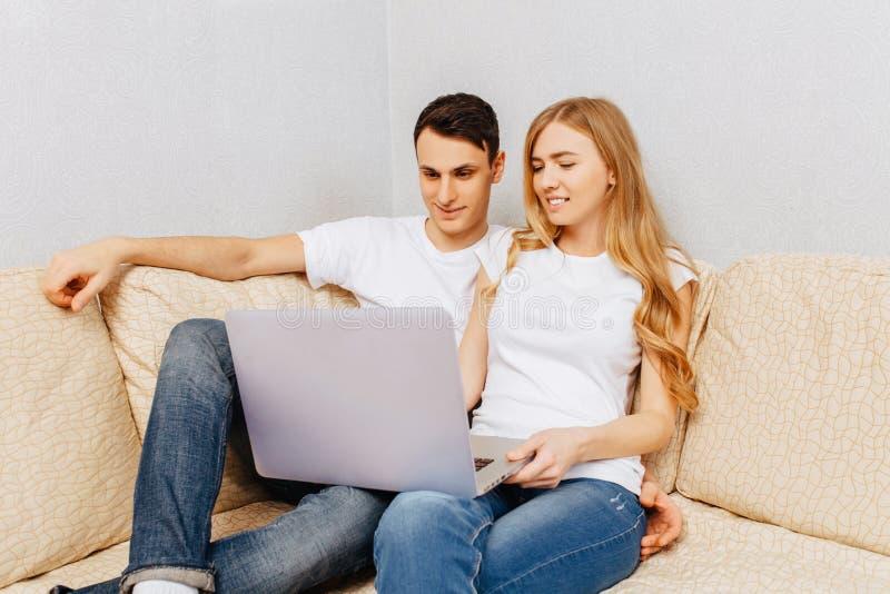 Schöne junge Paare, Mann und Frau, die einen Laptop, das Umarmen und das Lächeln, zu Hause sitzend auf der Couch verwendet stockfoto